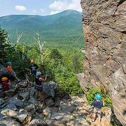Climbing guide Joan Veilleux sets up the belay for Owen Tuttle before he climbs Square Ledge in New Hampshire's White Mountains.