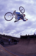 BMXer gets air off half-pipe, U.K, 1990s.