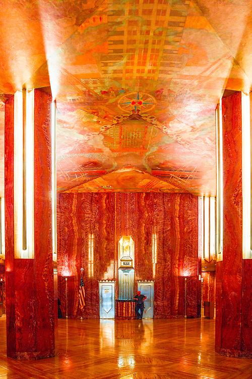 An Art Deco temple, the main lobby of the Chrysler Building is lined with red Moroccan marble and crowned by a tremendous mural covering the entire ceiling