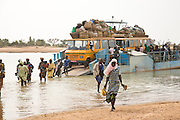 Degenné, Mali, 2009 -A cargo ferry unloads passengers and vehicles returning from the market day in Djenné. Sandbars along the bank of the Niger River have prevented the ferry from getting closer to shore forcing the vehicles and passengers to make their way through shallow water to the beach.