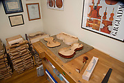 The workbench of Boston violin maker Christopher White displays a violin body, top, neck and a shaping frame for bending the sides.