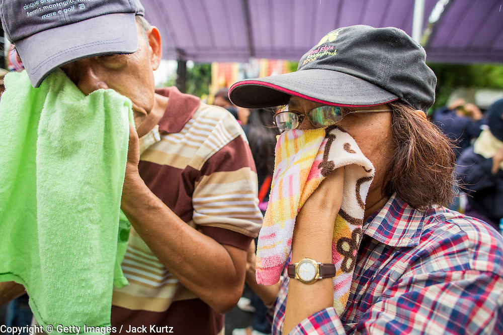 24 NOVEMBER 2012 - BANGKOK, THAILAND: A couple tries to get tear gas out of their eyes after they were gassed by Thai riot police during a large anti government, pro-monarchy, protest  on November 24, 2012 in Bangkok, Thailand. The Siam Pitak group, which sponsored the protest, cited alleged government corruption and anti-monarchist elements within the ruling party as grounds for the protest. Police used tear gas and baton charges againt protesters.       PHOTO BY JACK KURTZ