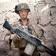 Location:<br /> Patrol Base Fires, Sangin District, Helmand Province, Afghanistan<br /> <br /> Unit: <br /> 3rd Squad, 1st Platoon, Bravo Company, 1st Battalion, 5th Marines<br /> <br /> Name and Rank: Lance Corporal David James Richvalsky<br /> <br /> Age: 19<br /> <br /> Hometown: Waialua, Hawaii<br /> <br /> Why did you join the Marine Corps?<br /> <br /> &quot;I joined the Marine Corps because I wanted to get off the island of Hawaii. I was slightly patriotic, and . . . I don&rsquo;t know, that&rsquo;s really the only reason I had. . . . I joined the Marine Corps out of all the other branches because I wanted to fight.&quot;<br /> <br /> Tell me about all of the weight you carry as a machine gunner:<br /> <br /> &quot;I carry obviously an M 240-B Machingun, and it weighs 27.1 pounds. And I carry 500 rounds for it on my body, but in the squad we carry eight hundred. A hundred rounds weighs 7.7 pounds, so if you do the math it adds up. I also carry a night optic for it, a 17 Charlie. It&rsquo;s not very heavy but it adds up too. I also carry PVS-14s which is like night vision, and I also carry about eight waters.&quot;<br /> <br /> &quot;I carry 35 pounds in rounds, 27 pounds in gun . . . I probably carry about maybe 60-65 pounds worth of gun gear only, not counting my flak and my water and all that shit.&quot;<br /> <br /> What does it do to your body?<br /> <br /> &quot;It feels like I&rsquo;m an old man, like I&rsquo;m just gonna fall apart.&quot;<br /> <br /> &quot;It&rsquo;s just what the Marine Corps does, they just break you down in boot camp. Like, they&rsquo;ll never really build you up.&quot;<br /> <br /> Describe your living conditions:<br /> <br /> &quot;I live in a fucking mud hut. It&rsquo;s just about three feet thick walls of mud, the hajjis live in. And right now it&rsquo;s actually pretty dirty just because I&rsquo;ve been disgusting and not cleaned it, and I got fleas because of the fucking chickens that run around.&quot;<br /> <br /> What is yo