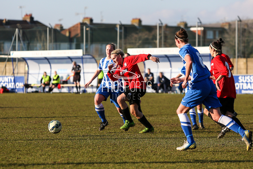 Hassocks' Gemma Craig is shadowed by Jay Blackie during the FA Women's Sussex Challenge Cup semi-final match between Brighton Ladies and Hassocks Ladies FC at Culver Road, Lancing, United Kingdom on 15 February 2015. Photo by Geoff Penn.