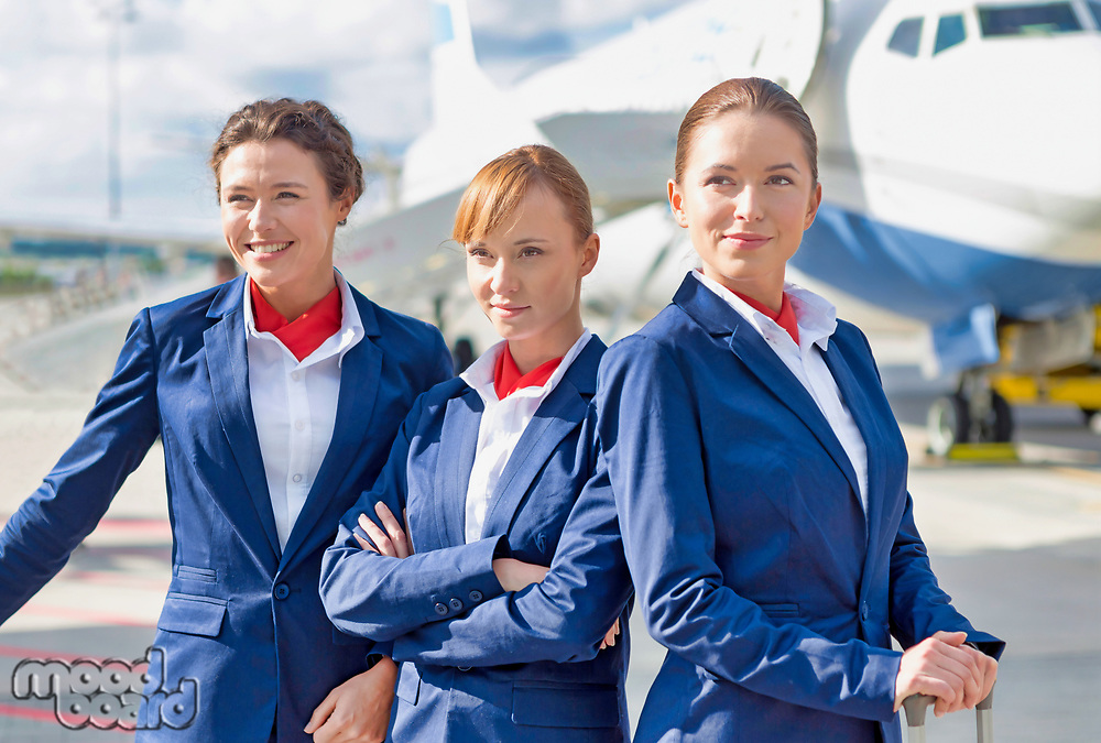 Photo of three confident flight attendants standing against airplane in airport