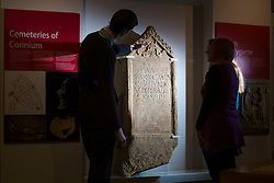 © Licensed to London News Pictures 25/01/2016, Cirencester, UK. Collections officer James Harris (L) looks at a unique Roman tombstone, found in February 2015, here on display for the first time at Corinium Museum in Cirencester. The tombstone was found near skeletal remains thought to belong to the person named on its inscription, making the discovery unique. After being found during excavation works on a fomer site of a garage, archaeologists said they believed it marked the grave of a 27-year-old woman called Bodica. Other theories point to it possibly belonging to a couple - as skeletal remains of women were found nearby.<br />