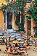 Chairs and tables in outdoor cafe, Roussillon de Provence, also known as the Ochre City.