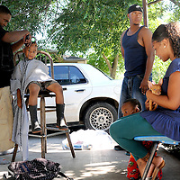 Twan Finley(left) cuts Alvin Melton Jr.'s(left center) hair infront of a friends house on South 4th Street in Temple, as Alvin Melton  Sr(right center)., Shay Cavitt(right) and Eric Melton Jr(between).hang out.