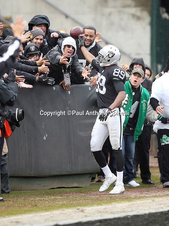 Oakland Raiders wide receiver Amari Cooper (89) gives the ball to a fan after catching a second quarter touchdown pass that cuts the Green Bay Packers lead to 14-13 with less than a minute left before halftime during the 2015 week 15 regular season NFL football game against the Green Bay Packers on Sunday, Dec. 20, 2015 in Oakland, Calif. The Packers won the game 30-20. (©Paul Anthony Spinelli)