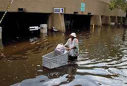 30 August, 2005. New Orleans Louisiana. Hurricane Katrina aftermath. <br /> An evacuee from the storm pushes her shopping trolly through the flood waters outside the Superdome.<br /> Photo Credit: Charlie Varley/varleypix.com