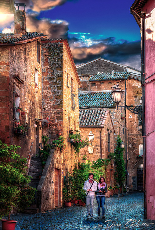 """""""Evening walk on the ancient cobbled streets of Orvieto""""...<br /> <br /> Orvieto is one of the most striking, memorable, and enjoyable hill towns in central Italy. Less than 90 minutes from Rome, Orvieto sits majestically high above the valley floor atop a big chunk of volcanic stone called tufa, and overlooking cypress-dotted Umbrian plains and vineyards. The ancient city rewards one with a peaceful and historical stroll back in time to the days of the Etruscans, who built this cliff top village over 2000 years ago for protection from their enemies. The ancient Etruscan wall still stands today presenting colorful cliffside views, and protecting the famous Duomo di Orvieto, the Palazzo del Popolo, and other antique treasures. The blue evening skies reflect on the shiny-worn cobblestone strada below as the last bit of sun illuminates the way for a delightful promenade."""