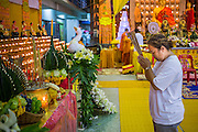 23 OCTOBER 2012 - HAT YAI, SONGKHLA, THAILAND: A woman prays at a shrine at Wat Ta Won Vararum, a Chinese Buddhist temple in Hat Yai. The Vegetarian Festival is celebrated in Thai-Chinese communities throughout Thailand. It is the Thai Buddhist version of the The Nine Emperor Gods Festival, a nine-day Taoist celebration celebrated in the 9th lunar month of the Chinese calendar. For nine days, those who are participating in the festival dress all in white and abstain from eating meat, poultry, seafood, and dairy products. Vendors and proprietors of restaurants indicate that vegetarian food is for sale at their establishments by putting a yellow flag out with Thai characters for meatless written on it in red.  PHOTO BY JACK KURTZ