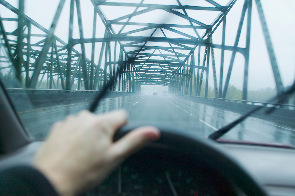 Drivers view through windshield crossing a bridge in the rain.