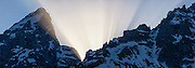 "Panorama telephoto view of ""crepuscular rays,"" or ""God Beams"" erupting as the sun sets behind the Grand Teton and Teewinot Mountain in Grant Teton National Park near Jackson Hole, Wyoming"