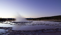 Purple and blue reflect in the geothermal pools at Great Fountain Geyser in Yellowstone National Park