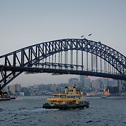 Sydney Bay during sunset seen from a ferry. Sydney Harbour Bridge.