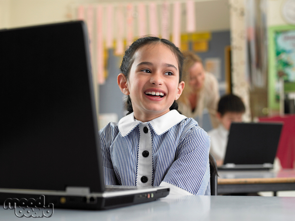 Elementary schoolgirl sitting by laptop in classroom smiling