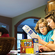 Ladlie looks at a box of graham crackers with her sister Molly, while recording the mass and volume of various household items for science class.