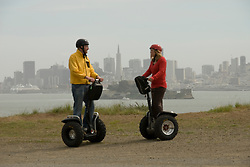 Couple on Segways, each on a Segway, on Angel Island State Park in San Francisco Bay, California, CA. Model released..Photo camari216-70415..Photo copyright Lee Foster, www.fostertravel.com, 510-549-2202, lee@fostertravel.com.