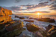 The sun strikes the red granite of Acadia near Thunder Hole at sunrise.