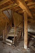 dilapidated wooden staircase in ruined house