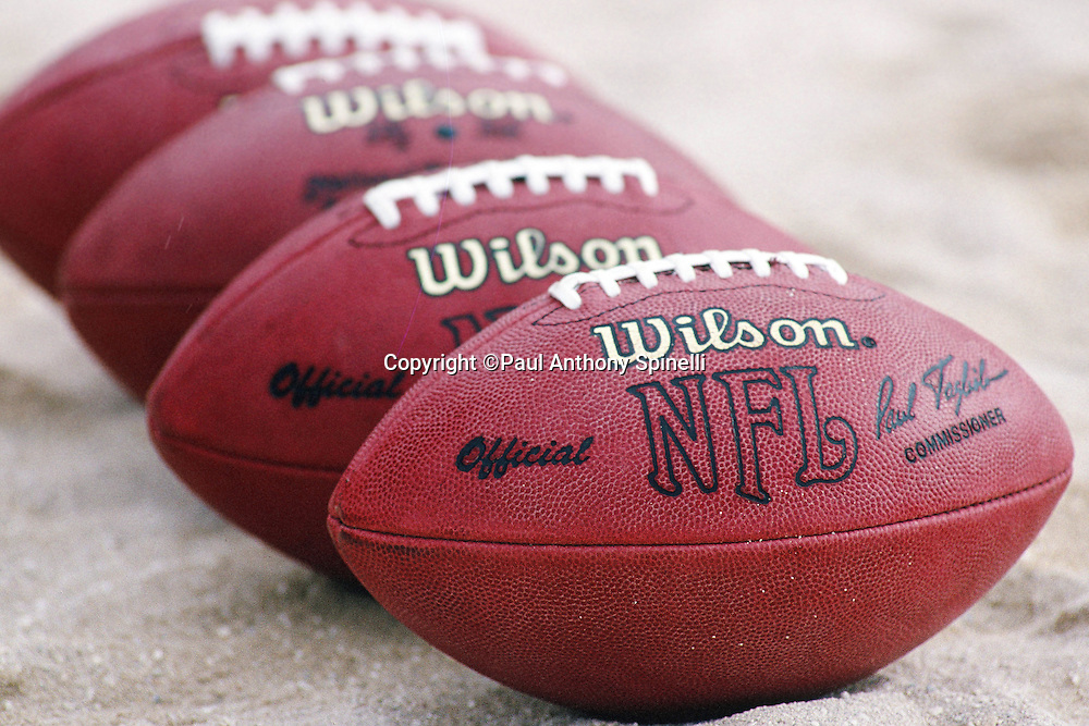 A line of footballs lies on the sand at an NFL beach football event at the 1997 NFL Pro Bowl between the AFC and the NFC on Jan. 31, 1997 in Honolulu. (©Paul Anthony Spinelli)