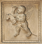 Winged cherub with a hobby horse, hitting it with a whip, representing childhood games and the fact that everything is not what it at first seems - we must look beyond the virtual to reality, from the coffered ceiling of the Oratory, carved in stone with 30 sections, each relating to a process in alchemy, in the Hotel Lallemant, a mansion built 1495-1518 in French Renaissance style by the Lallemant merchant family, in Bourges, Centre Val de Loire, France. The sculptural decoration on the building, made by both French and Italian sculptors, has been interpreted by Fulcanelli and others as having an alchemical symbolism. Since 1951 the building has housed the Musee des Arts Decoratifs and it was listed as a historic monument in 1840. Picture by Manuel Cohen