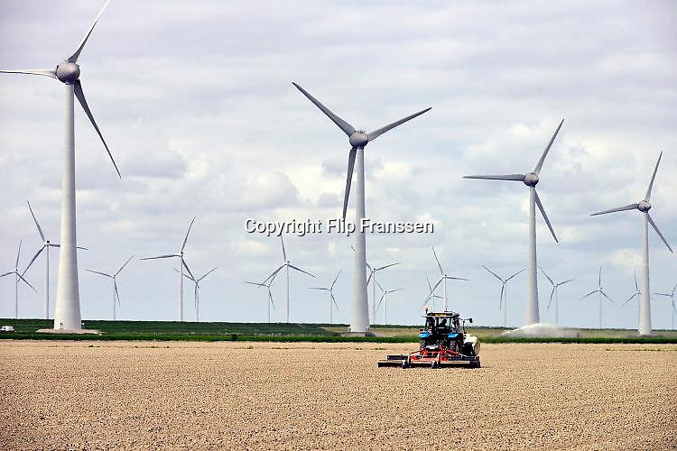 Nederland, the Netherlands, Urk, 9-5-2017 NOP Agrowind, energiebedrijf RWE Essent en Westermeerwind exploiteren een windpark op land en in het water van het IJsselmeer. De stroomproducent bouwde hier windmolens die 5 megawatt op land, en 3 megawatt op zee produceren. Siemens leverde turbines. Landbouw, een trekker rijdt over het land, de akker, het akkerland, de landbouwgrond FOTO: FLIP FRANSSEN