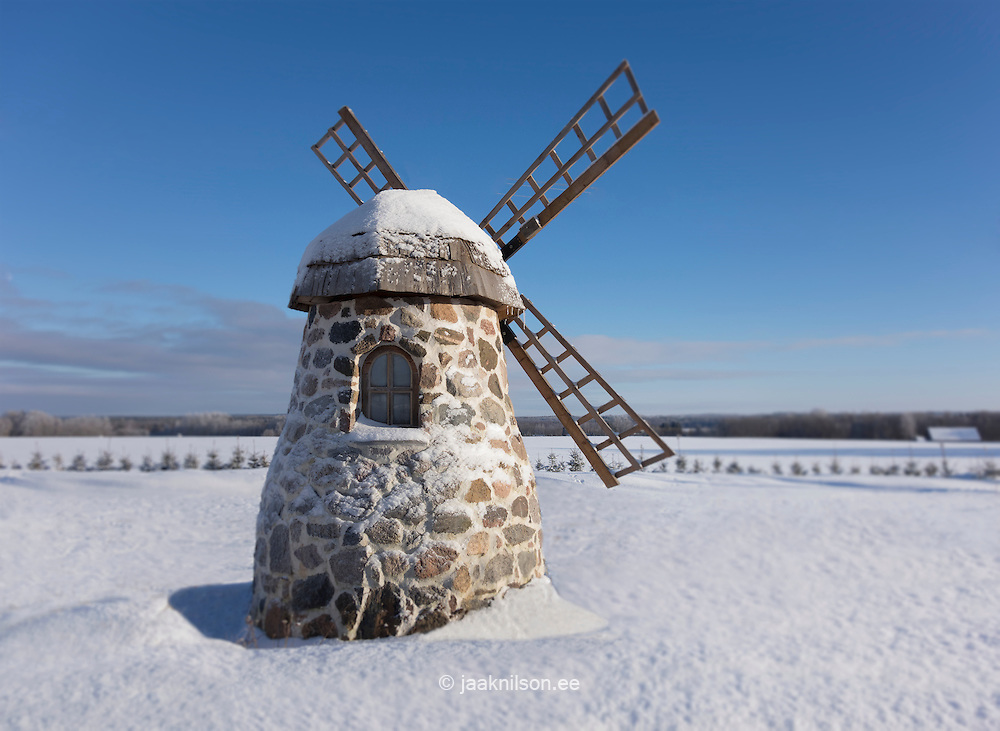 Old stone windmill on snowy landscape at winter. Restroom, toilet or outhouse.