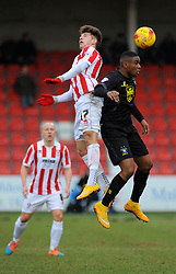Cheltenham Town's Zack Kotwica and Bury's Kelvin Etuhu challenge for the ball in mid-air.  - Photo mandatory by-line: Nizaam Jones - Mobile: 07966 386802 - 14/02/2015 - SPORT - Football - Cheltenham - Whaddon Road - Cheltenham Town v Bury - Sky Bet League Two