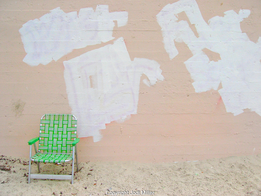 A green lawn chair in front of a pink wall on the beach.
