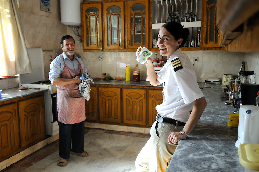 "Pilot, Danielle Aitchison, age 28, with her chef Mr. Flowers at her crew house in Kabul.  Daniel flies in Afghanistan for The United Nations Humanitarian Air Service (UNHAS).   ...When asked about flying in a war zone, she says,  ""I'm just a normal average female.  My job is maybe a little different to some, but I have the same feminine side as other women.  I don't have any trouble going back to New Zealand relating to people.  I'm just a regular chick.""."