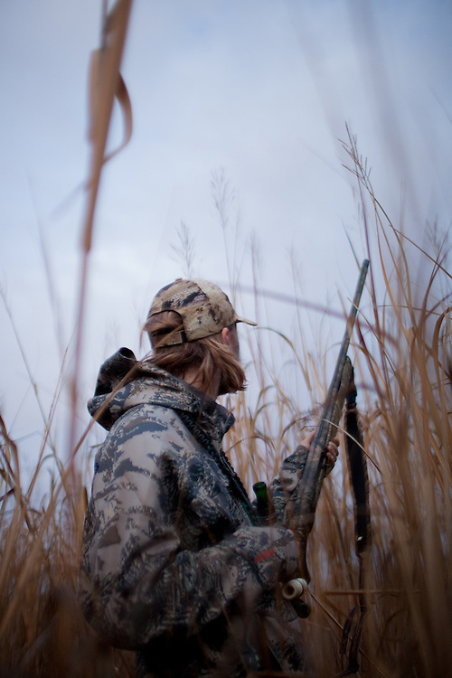 Waterfowl hunter standing in a marsh waiting on ducks.