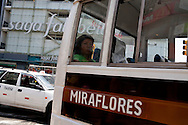 A woman rides a bus in the wealthy Miraflores neighborhood on Saturday, Apr. 4, 2009 in Lima, Peru.