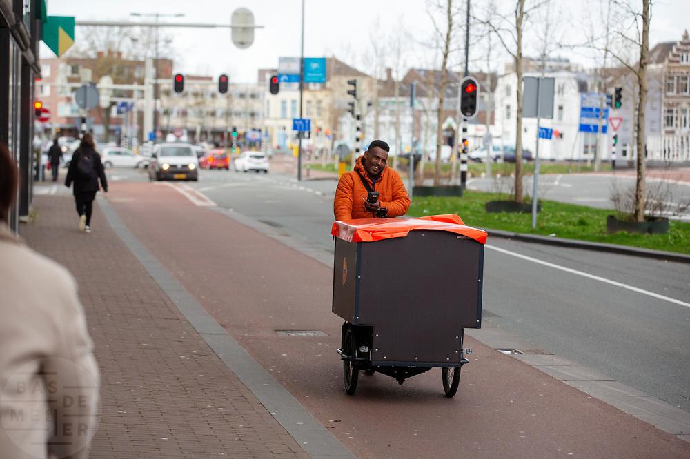 In Utrecht rijdt een bezorger van PostNL met een bakfiets.<br /> <br /> In Utrecht a postman rides on a cargo bike.