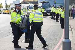 London, UK. 4 September, 2019. Metropolitan Police officers remove an anti-nuclear activist from one of the two main access roads to ExCel London during protests on the third day of a week-long carnival of resistance against DSEI, the world's largest arms fair. The third day's protests were organised by the Campaign for Nuclear Disarmament (CND) and Trident Ploughshares.