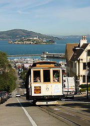 California, San Francisco: A Cable Car climbs Hyde Street to Chestnut, with Alcatraz in the background..Photo #: 4-casanf77889.Photo © Lee Foster 2008