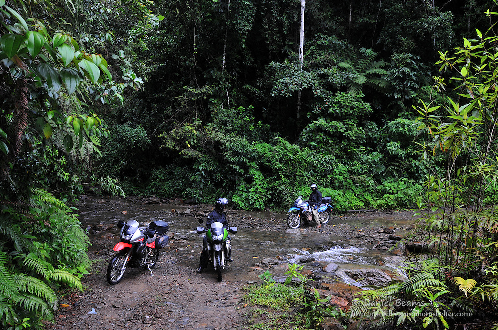 Motorcycles crossing a stream near Consata, Bolivia