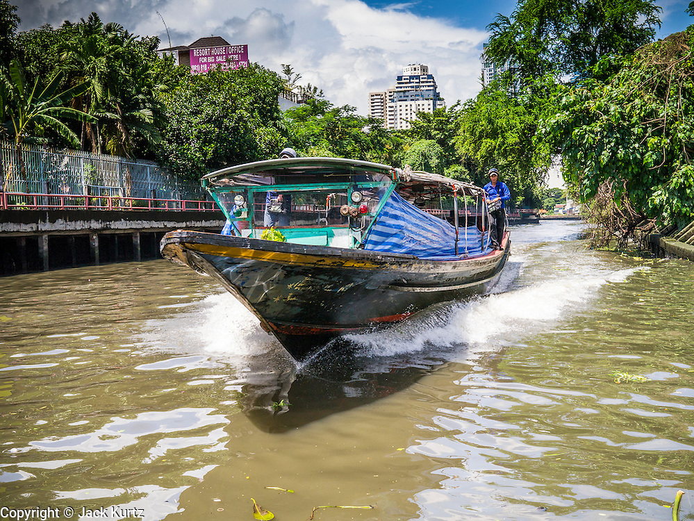 10 OCTOBER 2012 - BANGKOK, THAILAND:  A fast boat on Khlong Saen Saeb approaches the AsokPetchaburi Pier in Bangkok. Bangkok used to be criss crossed by canals (called Khlongs in Thai) but most have been filled in and paved over. Khlong Saen Saeb is one of the few remaining khlongs in Bangkok with regular passenger boat service. Boats and ships play an important in daily life in Bangkok. Thousands of people commute to work daily on the Chao Phraya Express Boats and fast boats that ply Khlong Saen Saeb. Boats are used to haul commodities through the city to deep water ports for export.     PHOTO BY JACK KURTZ