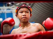 28 JULY 2013 - BANGKOK, THAILAND:  A young boxer gets ready for his bout at the ASEAN Muay Thai Championship at MBK shopping center in Bangkok.      PHOTO BY JACK KURTZ