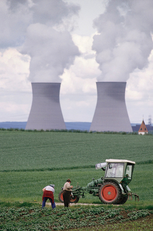 Nuclear energy: Nuclear Power Plant cooling towers punctuate the agrarian German countryside, with a farmer and his wife working in the foreground, Offingen, Germany. (1987) .