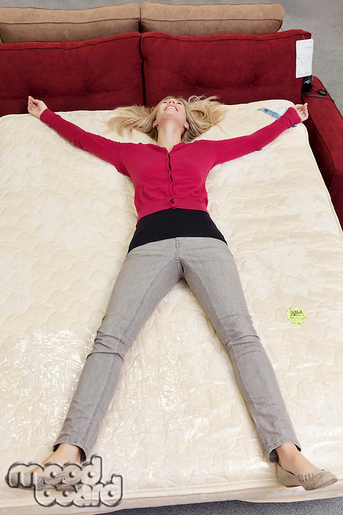 High angle view of woman lying on mattress in furniture store