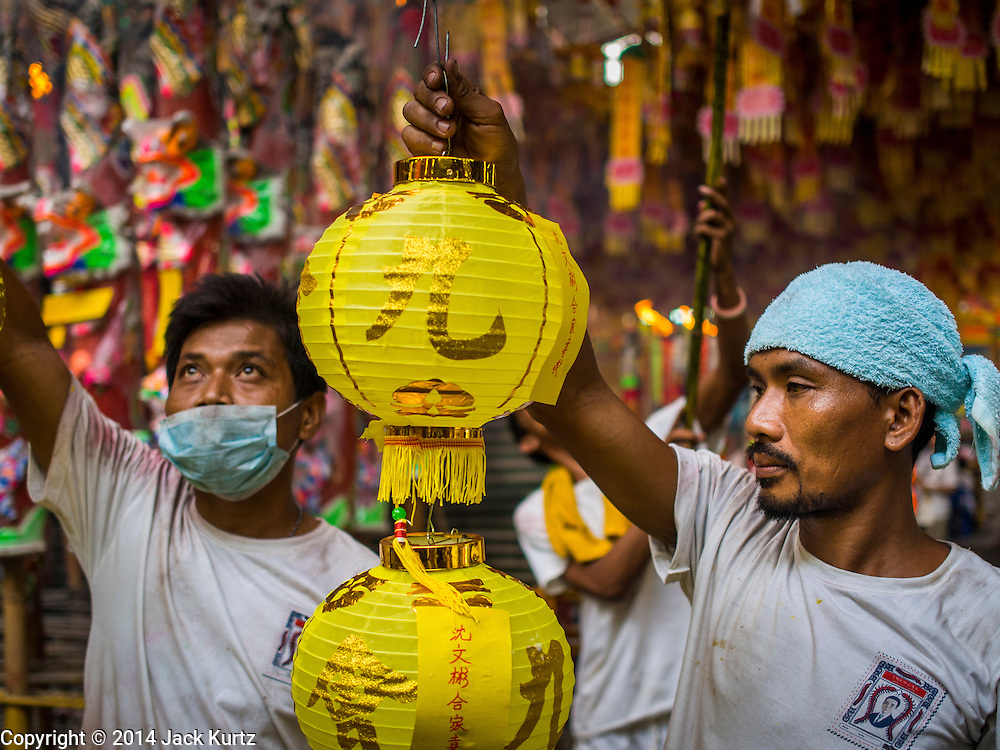 27 SEPTEMBER 2014 - BANGKOK, THAILAND: A temple attendant holds up paper lanterns during the celebration of the Vegetarian Festival at the Chow Su Kong Shrine in Talat Noi, a Chinese enclave in Bangkok. The Vegetarian Festival is celebrated throughout Thailand. It is the Thai version of the The Nine Emperor Gods Festival, a nine-day Taoist celebration beginning on the eve of 9th lunar month of the Chinese calendar. During a period of nine days, those who are participating in the festival dress all in white and abstain from eating meat, poultry, seafood, and dairy products. Vendors and proprietors of restaurants indicate that vegetarian food is for sale by putting a yellow flag out with Thai characters for meatless written on it in red.    PHOTO BY JACK KURTZ