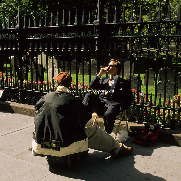 shoe cleaner cleaning. business man in front of Trinity  church and cemetery lower  Manhattan  New York  Usa ///  cireur de chaussure et business man devant Trinity  church et cimetière.  downtown  Manhattan  New York  USa ///  L004204  /  P100428