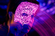 Man quickly covers face with a glowing opera mask.Black light