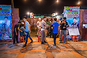 22 NOVEMBER 2013 - BANGKOK, THAILAND: Sailors with the Royal Thai Navy provide security at a Prathom Bunteung Silp mor lam show in Bangkok. There is usually a lot of drinking at the shows and brawls frequently break out at the end of the night. Mor Lam is a traditional Lao form of song in Laos and Isan (northeast Thailand). It is sometimes compared to American country music, song usually revolve around unrequited love, mor lam and the complexities of rural life. Mor Lam shows are an important part of festivals and fairs in rural Thailand. Mor lam has become very popular in Isan migrant communities in Bangkok. Once performed by bands and singers, live performances are now spectacles, involving several singers, a dance troupe and comedians. The dancers (or hang khreuang) in particular often wear fancy costumes, and singers go through several costume changes in the course of a performance. Prathom Bunteung Silp is one of the best known Mor Lam troupes in Thailand with more than 250 performers and a total crew of almost 300 people. The troupe has been performing for more 55 years. It forms every August and performs through June then breaks for the rainy season.     PHOTO BY JACK KURTZ