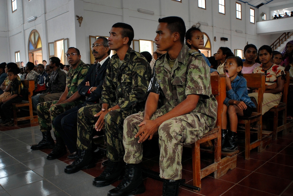 "Major Alfredo Reinado at Sunday Mass in Maubisse, East Timor,  11 June 2006. (3rd from left). Later, at a press conference in Maubisse, rebel leaders Major Alfredo Reinado and Manuel Tilman (2nd from left) announce they are planning a conference to seek ways of modifying East Timor's constitution to allow greater power for President Xanana Gusmao. Current Prime Minister Mari Alkitiri ""does not have the confidence of the people"" said Tilman. ""Time is the most dangerous weapon"" said Reinado."