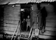 Mulyati and her mother, Jelawat No, come to the door of their makeshift raised hut on the edge of the Borneo rainforest.  Pa Tik I Penan settlement, near Bario, Sarawak, Malaysia.