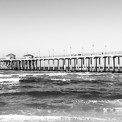 Huntington Beach Pier black and white panorama picture. Panoramic photo ratio is 1:3. Huntington Beach Pier is a registered historic place.  Huntington Beach is also known as Surf City USA and is a seaside beach city along the Pacific Ocean in Southern California.