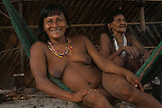 Huaorani Indian, Kope Tega relaxing in her hammock inside her hut. This is usually the only furnishing in the huts.<br /> Bameno Community. Yasuni National Park.<br /> Amazon rainforest, ECUADOR.  South America<br /> This Indian tribe were basically uncontacted until 1956 when missionaries from the Summer Institute of Linguistics made contact with them. However there are still some groups from the tribe that remain uncontacted.  They are known as the Tagaeri & Taromenane. Traditionally these Indians were very hostile and killed many people who tried to enter into their territory. Their territory is in the Yasuni National Park which is now also being exploited for oil.